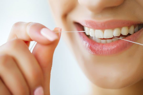 dental-care-woman-with-beautiful-smile-using-floss-teeth-image_118454-4125